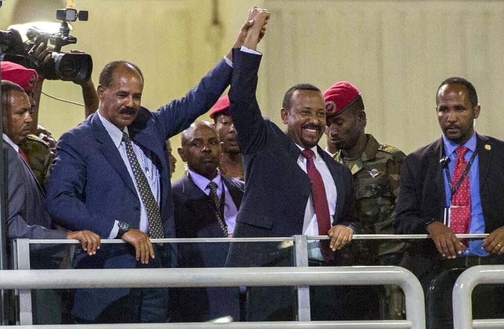 Premiê etíope, Abiy Ahmed (centro), de mãos dadas com o presidente da Eritreia, Isaias Afwerki,  falam ao público na capital da Etiópia — Foto: Mulugeta Ayene/AP