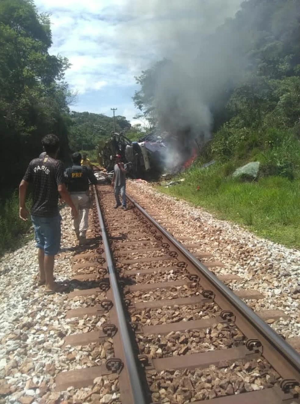 Pessoas são vistas nos trilhos sobre os quais o ônibus caiu em acidente na BR-381, em MG — Foto: Reprodução/GloboNews