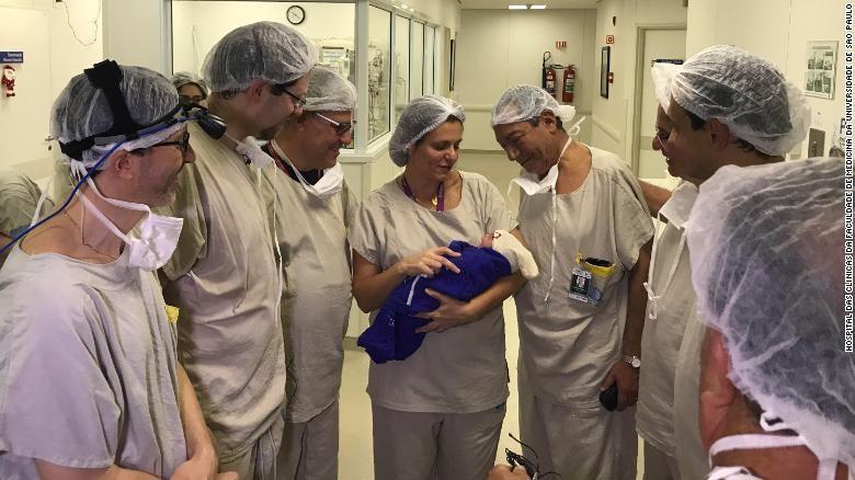 Equipe de médicos segura o recém nascido. (Foto: Hospital das Clínicas)