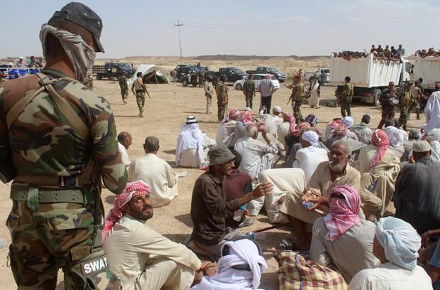 Quando deixam a cidade, homens adultos e adolescentes são controlados separadamente (Foto: MOADH AL-DULAIMI/AFP)
