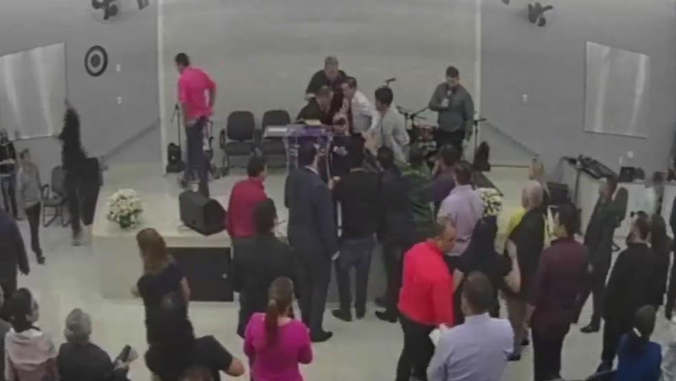 homens sobem no palco e um deles agarra o agressor na igreja (Foto: Reprodução/Facebook)