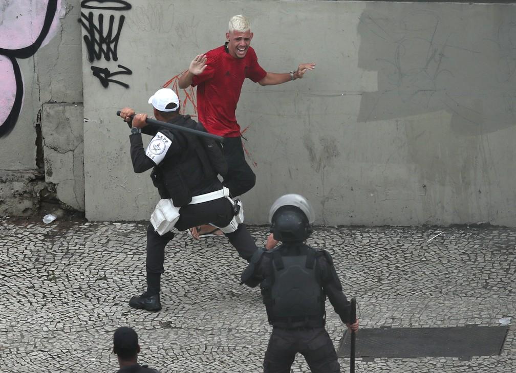 Policial aponta cassetete para torcedor do Flamengo após confusão no final do desfile no Rio neste domingo (24) — Foto: Ricardo Moraes/Reuters