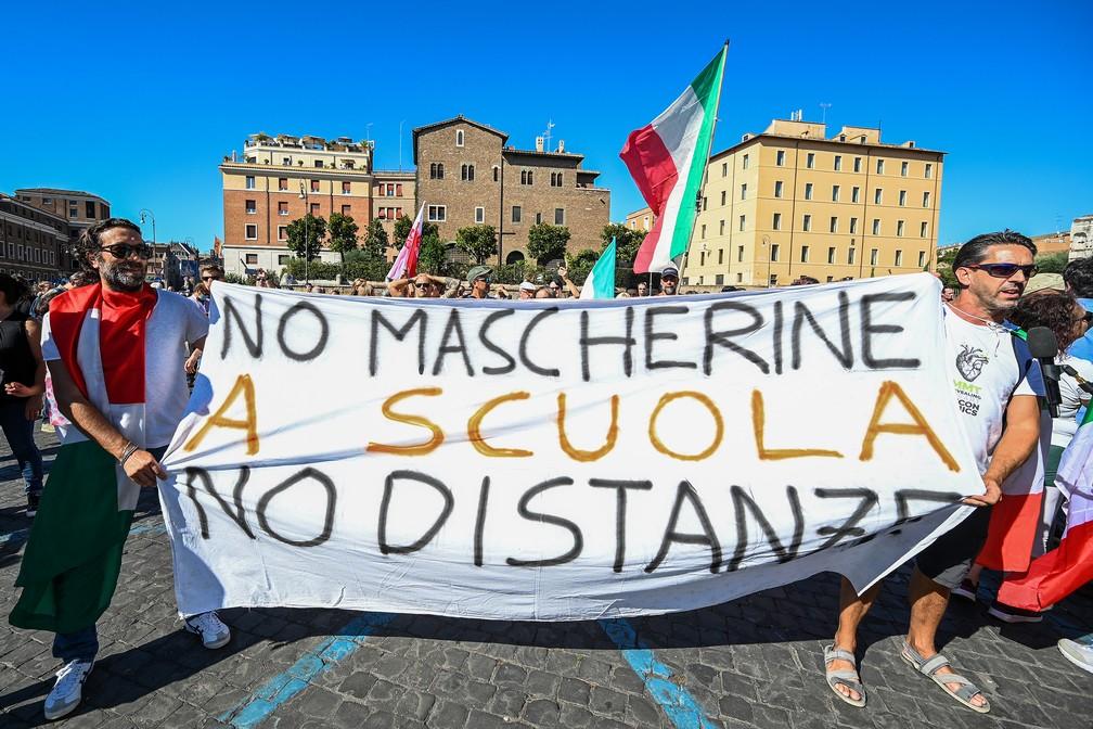 Grupo de manifestantes leva faixas e cartazes contra o uso de máscaras, em Roma — Foto: Vincenzo Pinto/AFP