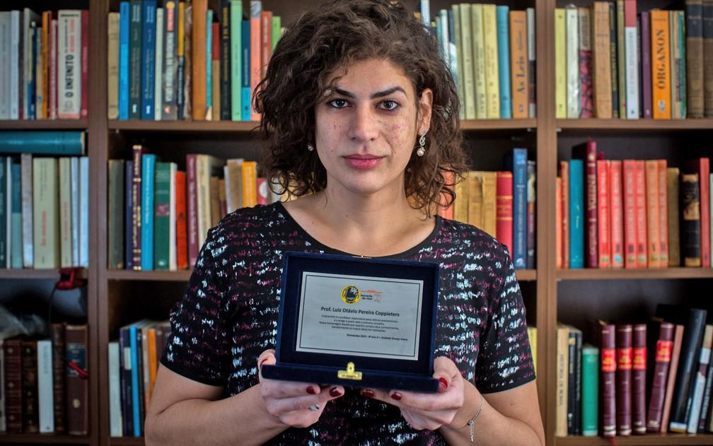 Professora Luiza Coppieters mostra homenagem que recebeu como paraninfo dos alunos quando ainda era chamado de professor Luiz — Foto: Victor Moriyama/G1/ Arquivo 2015