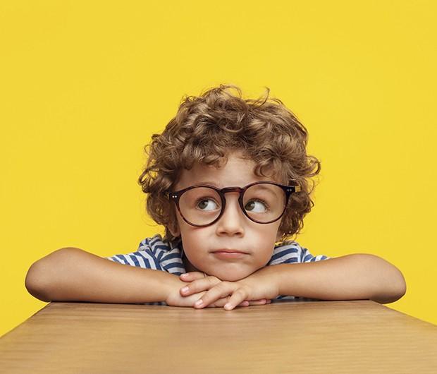 Menino loiro de cabelo cacheado com óculos olhando para cima com queixo em cima das mãos em fundo amarelo (Foto: Thinkstock)