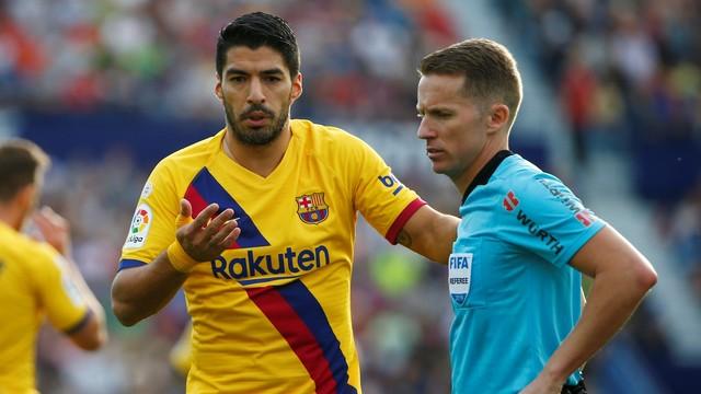 Luis Suárez argumenta com o árbitro depois de ser punido injustamente com cartão amarelo