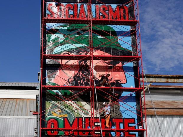 Homem pinta mural em Havana com representação de Fidel Castro e os dizeres 'socialismo ou morte' (Foto: REUTERS/Stringer)