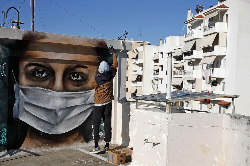 Um jovem grego de 16 anos de idade dá retoques no grafite de uma mulher usando uma máscara, inspirado na pandemia do coronavírus, no telhado do prédio onde ele mora em Atenas. Foto de terça-feira (17) — Foto: Thanassis Stavrakis/AP