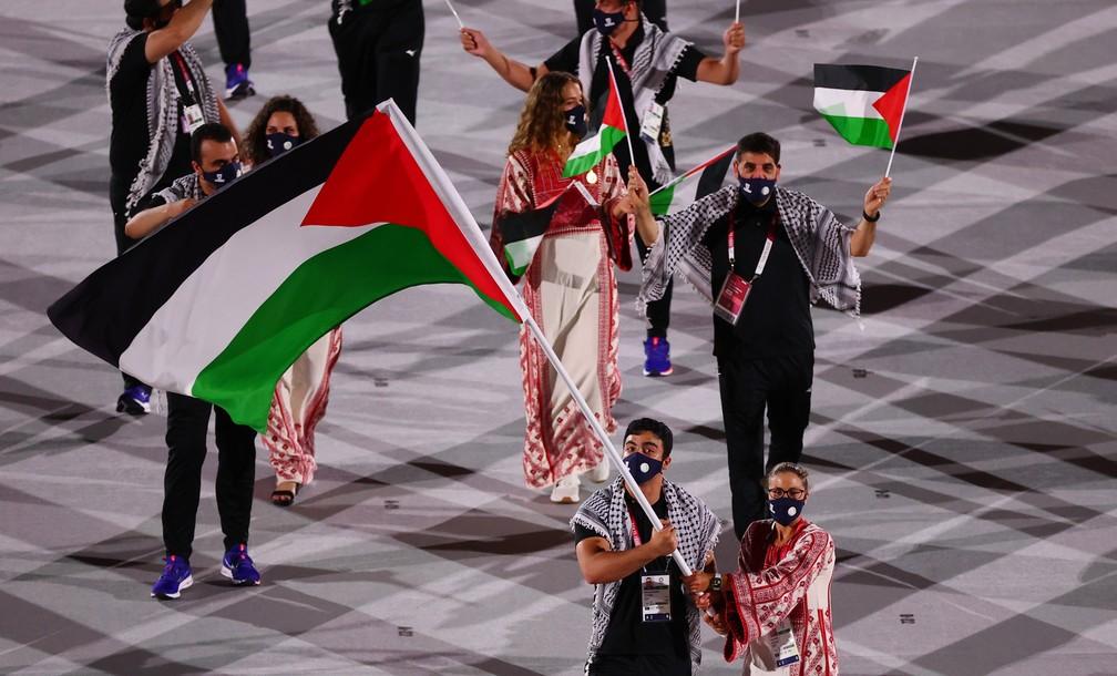 Dania Nour e Mohammed Hamada levam a bandeira da Palestina durante a cerimônia de abertura dos Jogos Olímpicos de Tóquio, no Japão — Foto: Mike Blake/Reuters