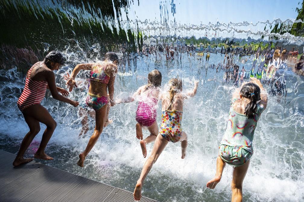 Meninas mergulham em cachoeira de parque em Washington D.C. em 28 de junho de 2021, em meio a uma onda de calor histórica que atinge grande parte dos Estados Unidos e do Canadá. Trechos dos Estados Unidos e do Canadá. — Foto: Jim Watson/AFP