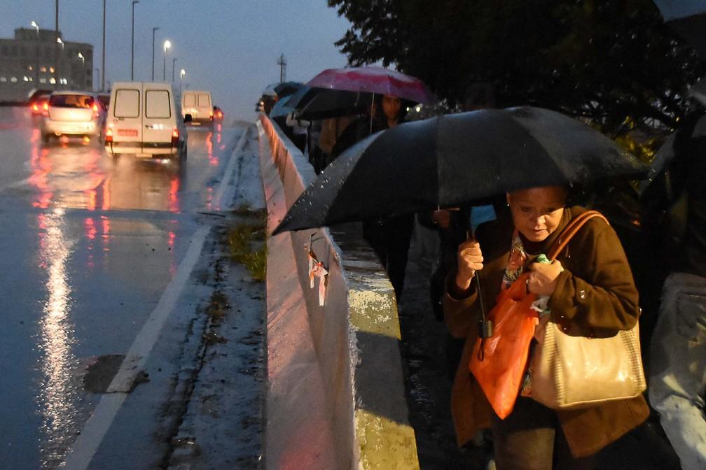 Pedestres se protegem da chuva na Ponte do Jaguaré, em São Paulo, na manhã desta quinta-feira (4) — Foto: Ronaldo Silva/Estadão Conteúdo