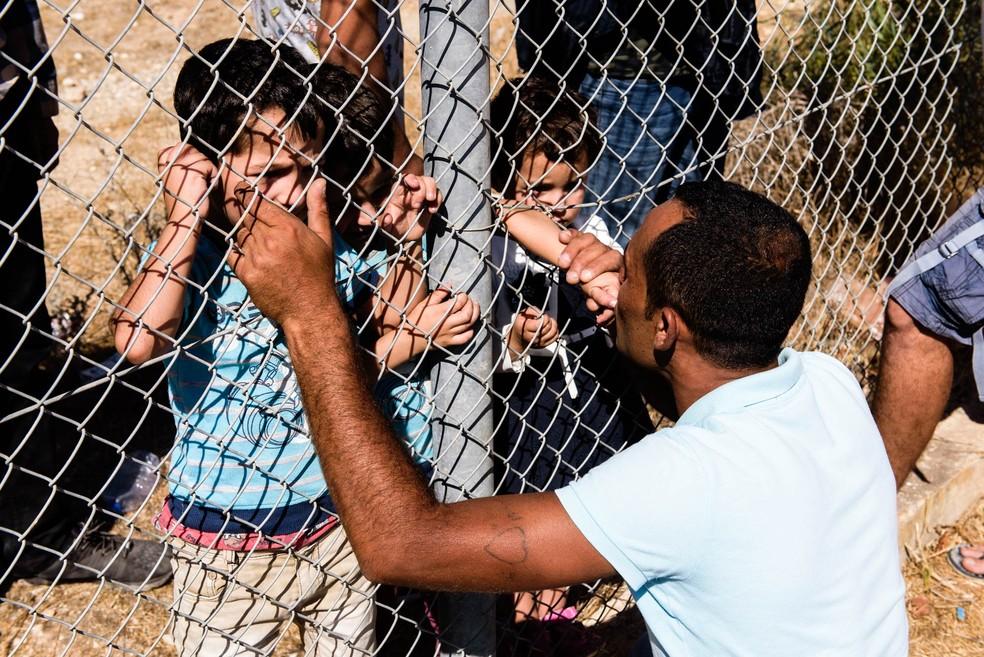 O sírio Ammar Hammasho se emocionou ao tocar e beijar os quatro filhos e a mulher no reencontro um ano após fugir da guerra civil da Síria até o Chipre. Separados por uma grade, os meninos se amontoaram para tocar o pai e matar as saudades depois de sobreviverem à viagem. O momento foi registrado neste domingo (10) (Foto: Iakovos Hatzistavrou/AFP)