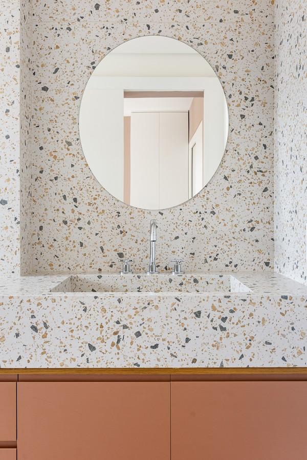 Cubas: Parede com pia suspensa revestidos de granilite, armário amadeirado em baixo e espelho redondo.
