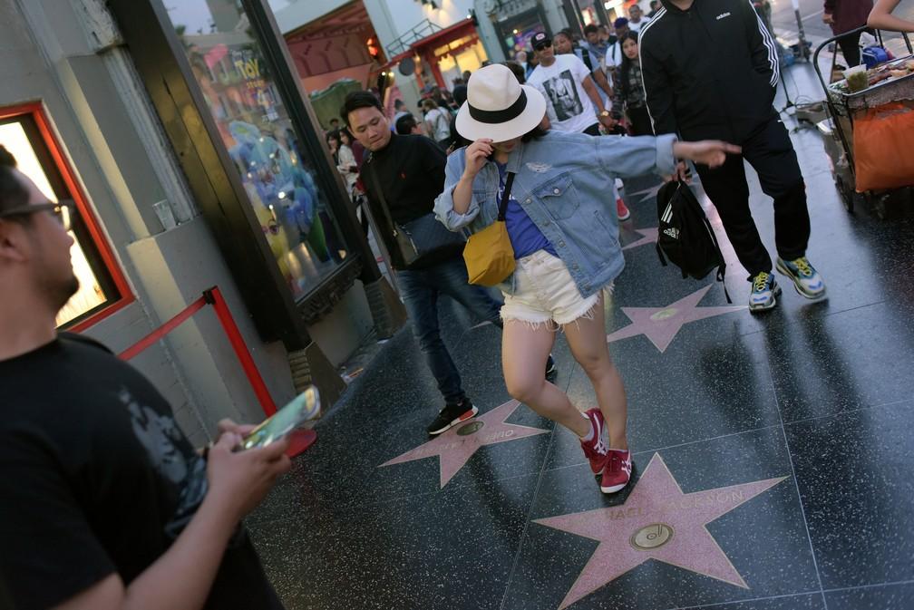 Fã posa diante de estrela de Michael Jackson na Calçada da Fama. Local deve receber homenagens ao cantor nesta terça-feira (25) — Foto: Agustin PAULLIER / AFP