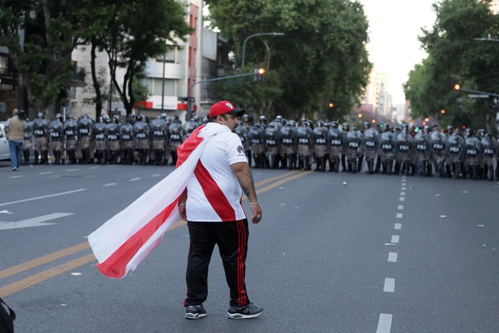 Um torcedor do River Plate diante de policiais preparados para ação em Buenos Aires: houve distúrbios nas ruas após o adiamento da final da Libertadores — Foto: Alberto Raggio/Reuters