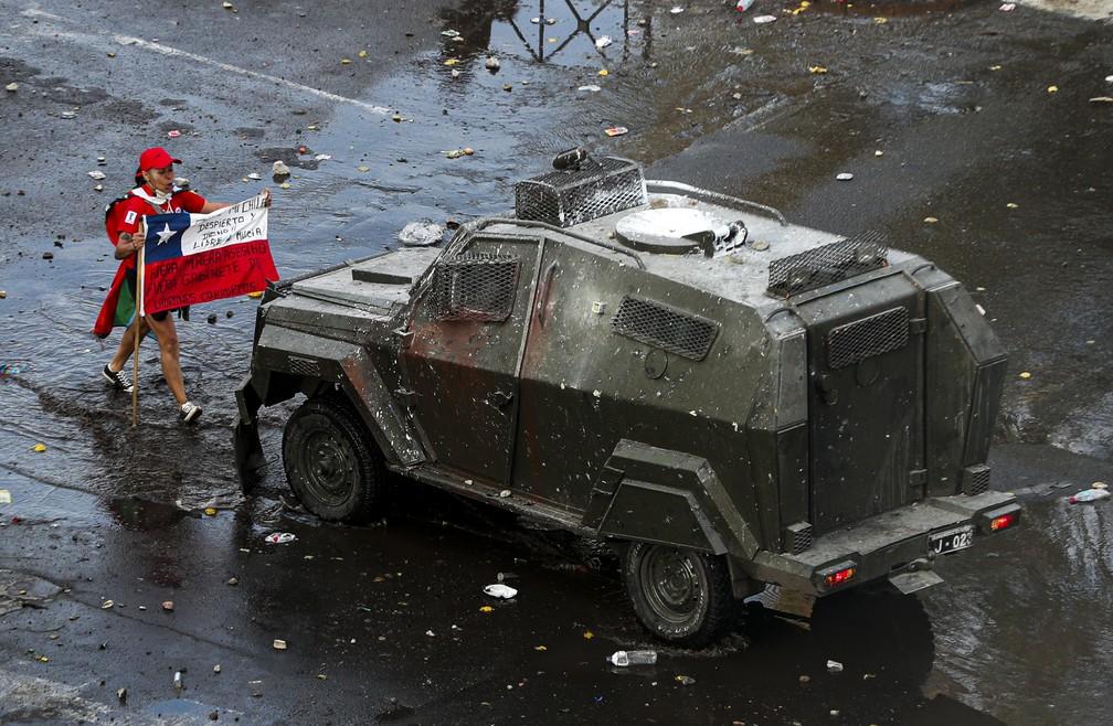 Manifestante segura bandeira do Chile em frente a blindado militar em protesto em Santiago nesta terça-feira (22) — Foto: Esteban Felix/AP Photo