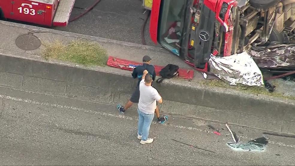 Um homem foi detido após caminhão tombar sobre carro na Avenida Brasil — Foto: Reprodução/ TV Globo