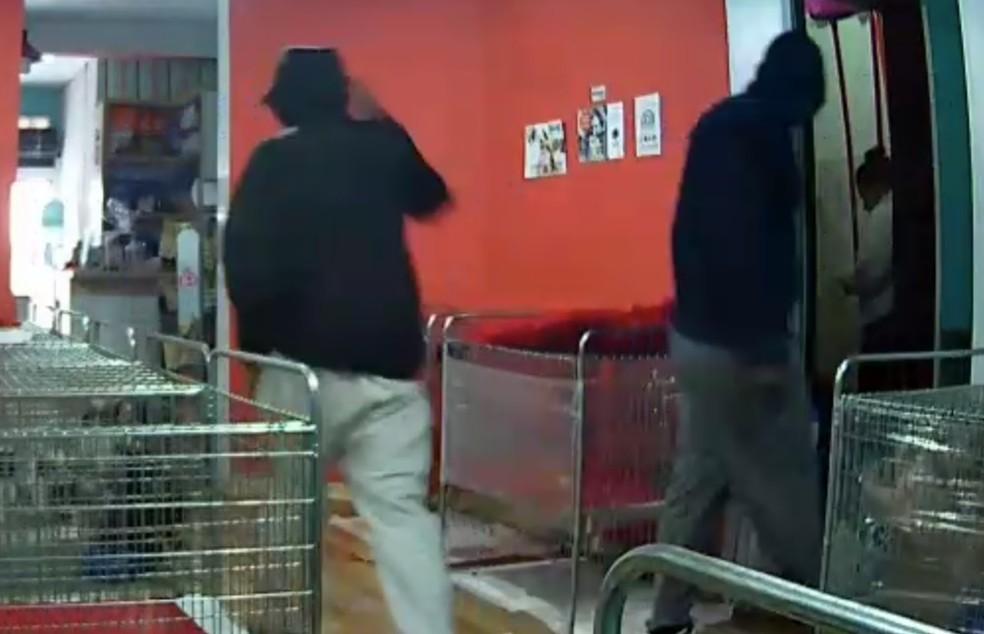 Homens deixam funcionária no estoque enquanto pegam os animais do pet shop, em Curitiba. (Foto: Divulgação)