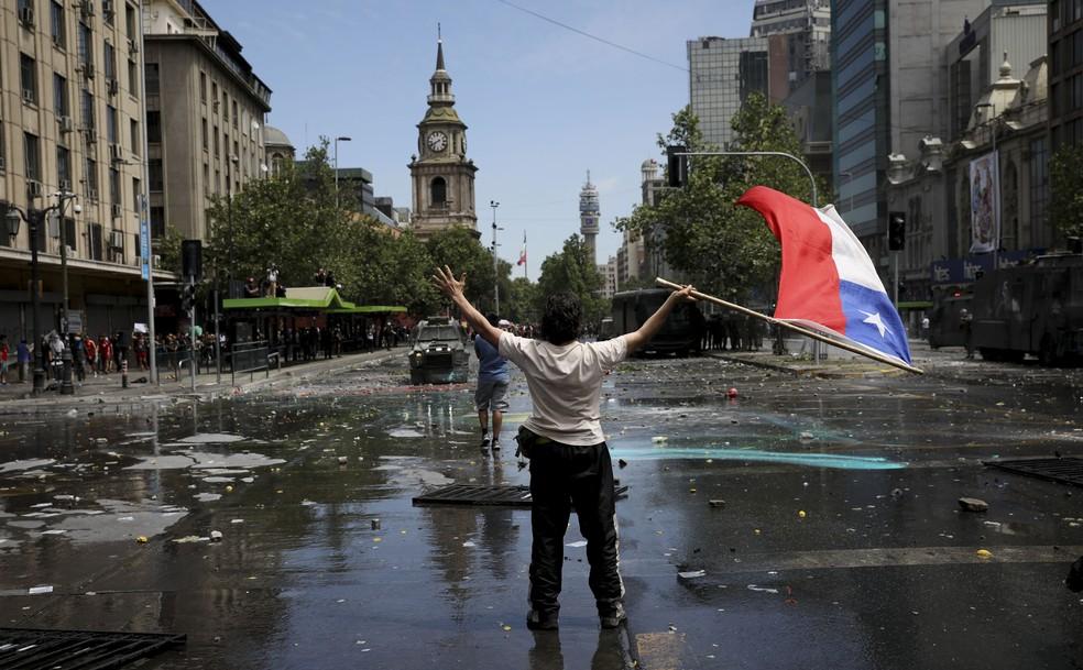 Manifestante balança bandeira do Chile em avenida de Santiago nesta quarta-feira (23) — Foto: Rodrigo Abd/AP Photo