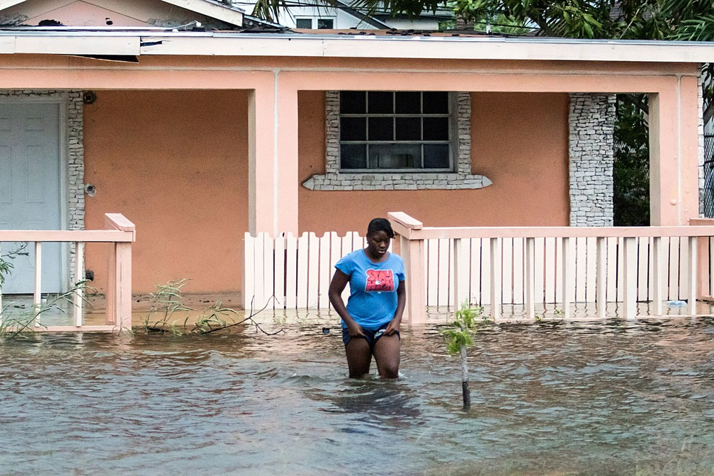 Mulher caminha em área alagada em Nasssau, nas Bahamas, na segunda-feira (2), na passagem do furacão Dorian — Foto: John Marc Nutt/ Reuters