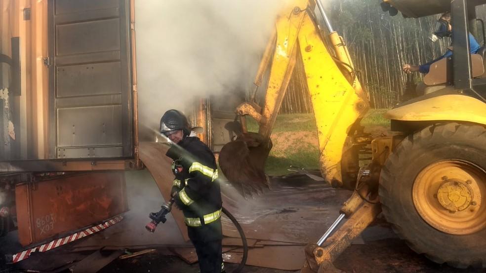 Foi necessária uma retroescavadeira para retirar o material de chapas de madeira do caminhão em Botucatu — Foto: Corpo de Bombeiros / Divulgação