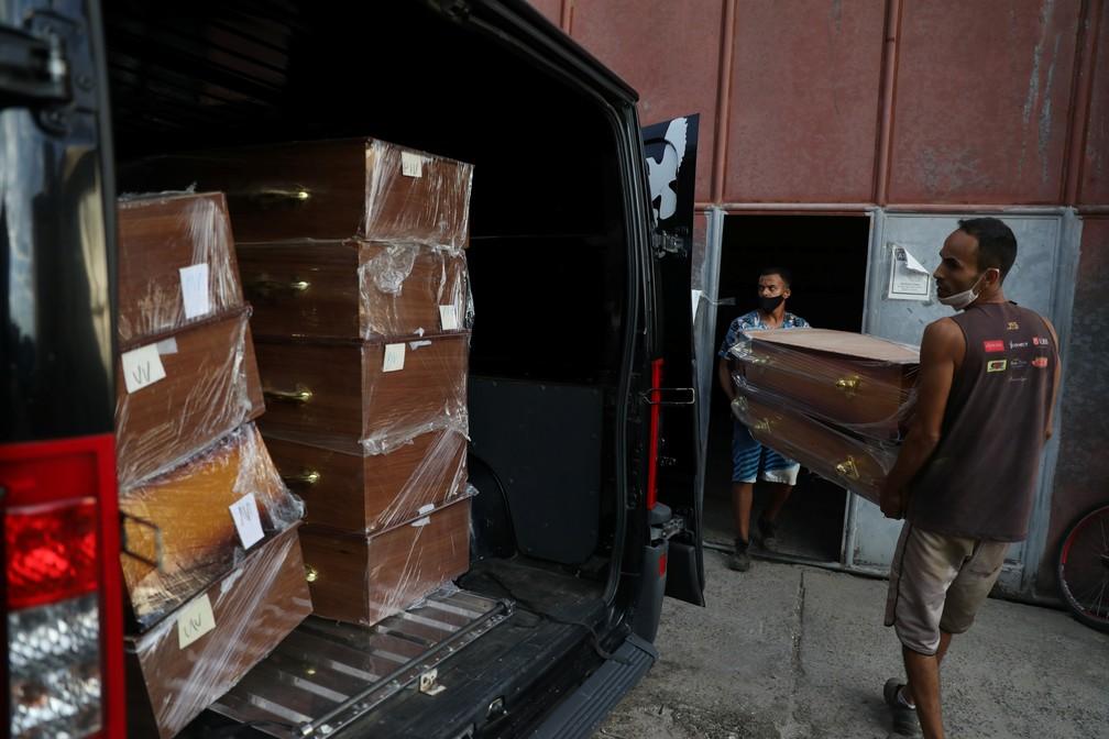 Trabalhadores colocam caixões em carro funerário em Nova Iguaçu, no Rio de Janeiro, em meio à pandemia do novo coronavírus (Covid-19) no Brasil em 9 de abril de 2021 — Foto: Pilar Olivares/Reuters