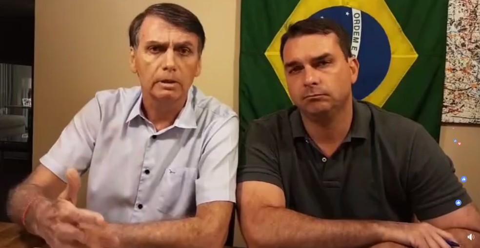 O candidato do PSL à Presidência, Jair Bolsonaro, ao lado do filho Flávio Bolsonaro, durante transmissão no Facebook — Foto: Reprodução