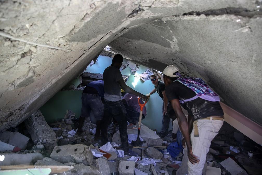 Grupo procura sobreviventes em uma casa destruída pelo terremoto em Les Cayes, Haiti — Foto: Joseph Odelyn/AP
