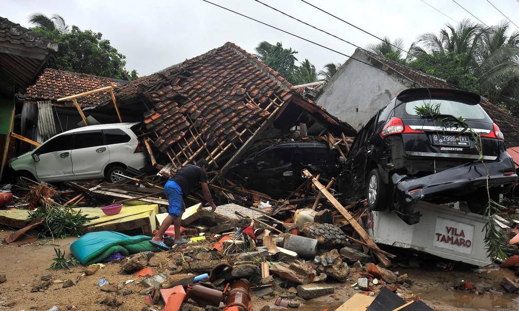 Moradores procura pertences entre os escombros após tsunami atingir a província de Banten, na Indonésia — Foto: Antara Foto/Asep Fathulrahman/ via REUTERS