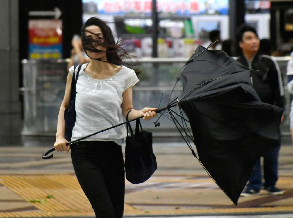 Mulher segura guarda-chuva quebrado durante passagem do tufão Jebi, em Osaka, no oeste do Japão, nesta terça-feira (4)  (Foto: Nobuki Ito / Kyodo News via AP)