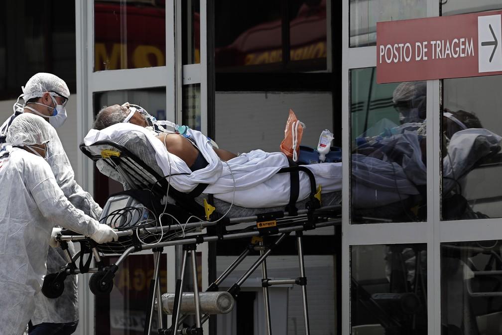 Profissionais de saúde entram com paciente com suspeita de Covid-19 de maca no HRAN, hospital público de Brasília, no dia 23 — Foto: Eraldo Peres/AP