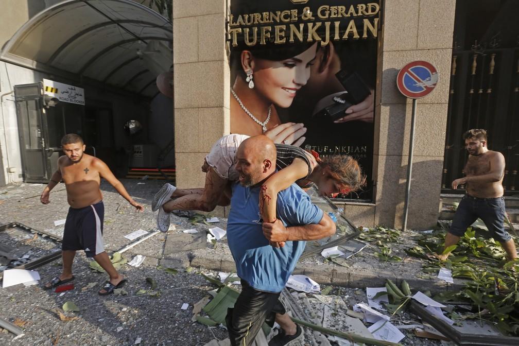 Ferido em explosão em Beirute é carregada — Foto: Marwan TAHTAH / AFP