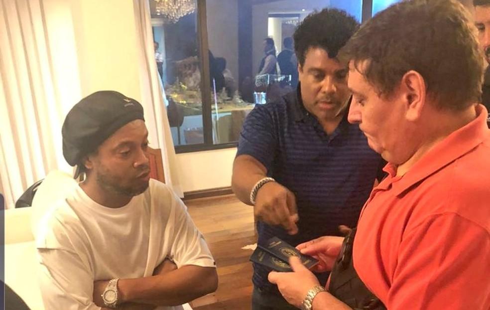 Ronaldinho e Assis mostram passaportes a fiscais do MP do Paraguai — Foto: Divulgação/Ministério Público do Paraguai
