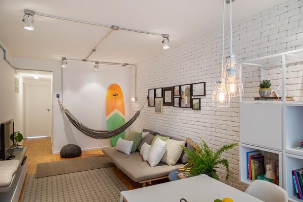 LIVING | Com 87 m², o apartamento da década de 60 foi modernizado, mas manteve o piso de taco original. rede da Collector 55. Fotos da Paredeira. Tapete grande da West Wing e tapete menor da Willer K. Tijolinhos na parede da Pedra Paulista. Futon da Trama (Foto: Rafael Renzo / Divulgação)