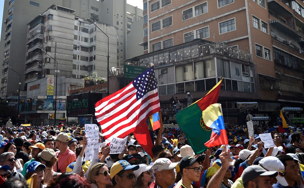 Bandeira dos Estados Unidos é vista no meio da multidão de simpatizantes do líder da oposição venezuelana, Juan Guaidó, que se autodeclarou presidente interino   — Foto: Federico Parra / AFP