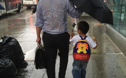 Foto do dia: pai dispensa o uso do guarda-chuva para proteger o filho