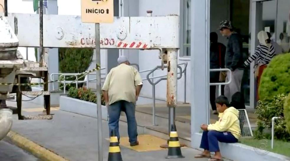 Clientes que precisaram ir à agência nos dias em que a máquina ficou no local precisavam se abaixar na calçada — Foto: TV TEM/Reprodução