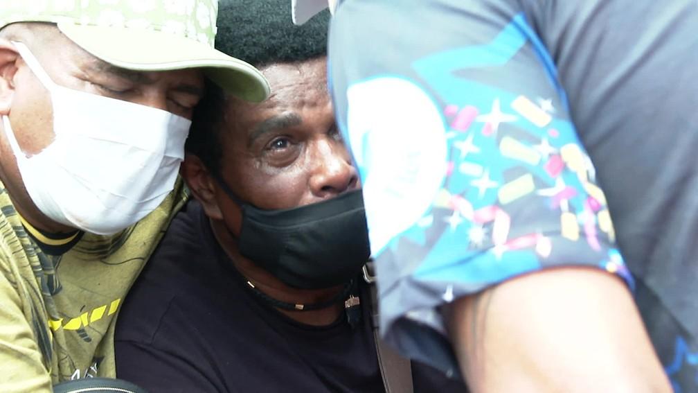 Neguinho da Beija-Flor é amparado por amigos no enterro do neto Gabriel  — Foto: Reprodução/TV Globo