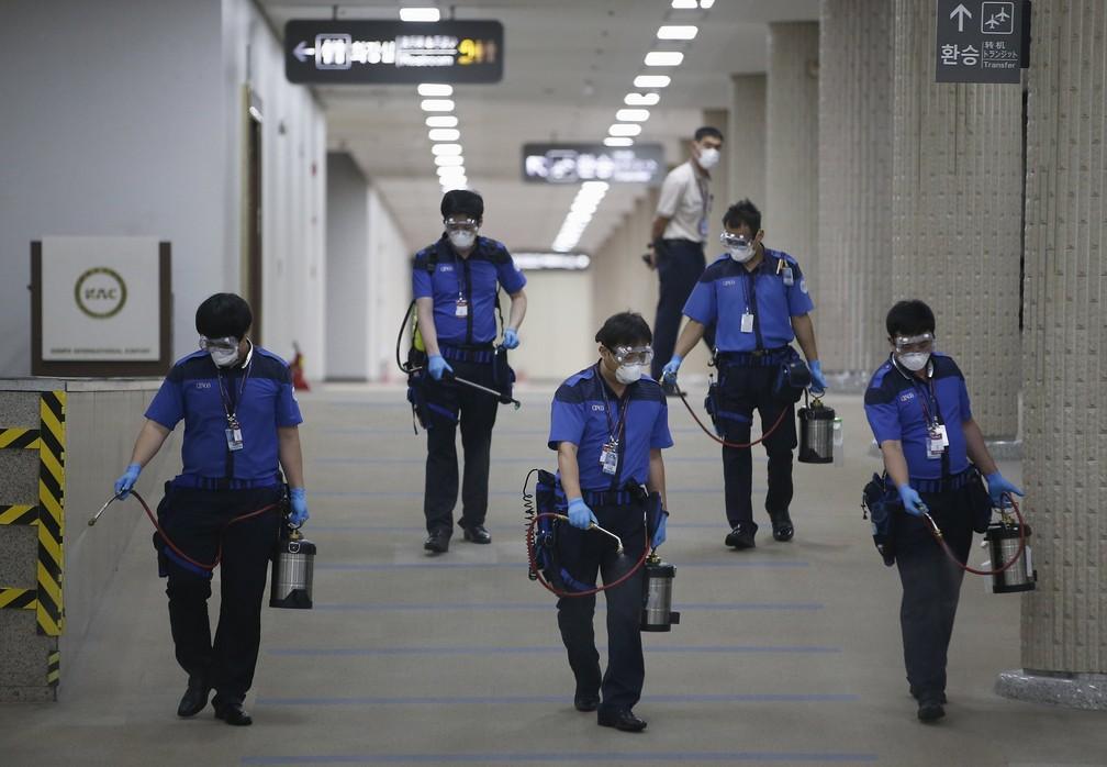 Empregados de uma companhia sanitária desinfetam chão do aeroporto internacional Gimpo, em Seul — Foto: Kim Hong-Ju