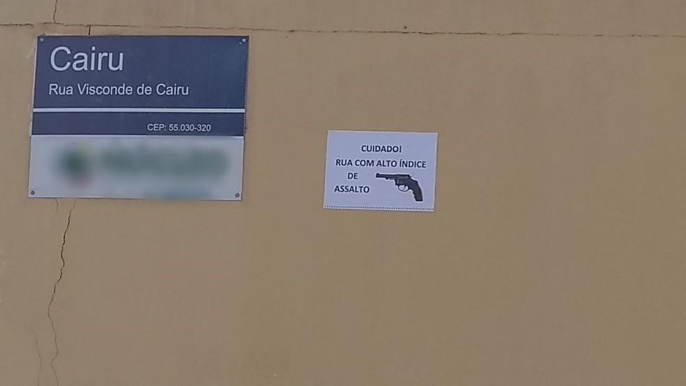 Placa visa alertar pessoas que passam pelo local sobre assaltos (Foto: Eliaquim Oliveira/TV Asa Branca)