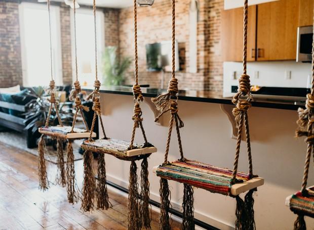 Os balanços na bancada trazem tranquilidade para o ambiente, enquanto os tecidos que decoram os assentos colorem dão cor  (Foto: Refine Studio/ Reprodução)
