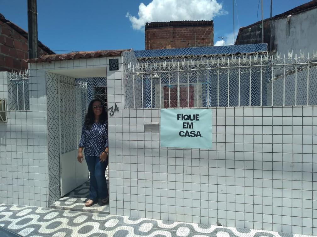 MACEIÓ - Pedagoga Cida Silva colou nesta terça (24) um cartaz no muro de casa, em Maceió, para mandar um recado sobre a orientação de isolamento social — Foto: Carolina Sanches/G1
