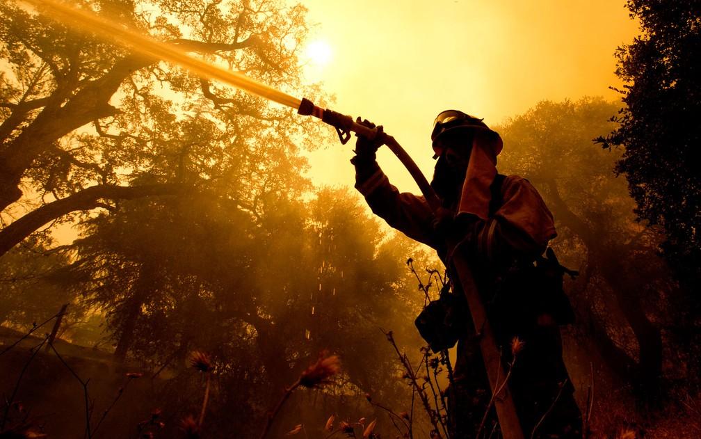 O bombeiro Jason Sheumann joga água em casa atingida por incêndio em Napa, na Califórnia, na segunda-feira (9) (Foto: AP Photo/Rich Pedroncelli)