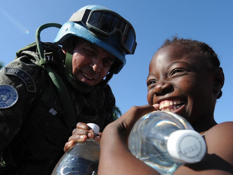 Militar brasileiro que integrava a Minustah, missão de paz da ONU no Haiti, entrega garrafas d'água para uma criança haitiana após o terremoto devastador ocorrido em janeiro de 2010 — Foto: Jewel Sawad/AFP/Arquivo