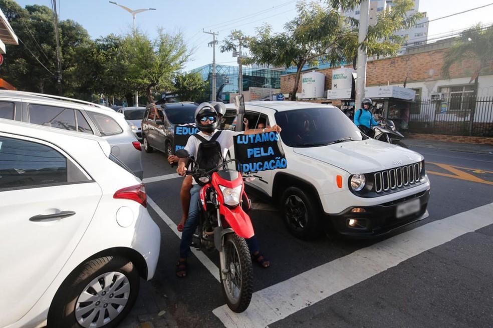 Durante o percurso, participantes da carreata buzinavam e exibiam cartazes pedindo a volta das aulas em Fortaleza — Foto: Thiago Gadelha