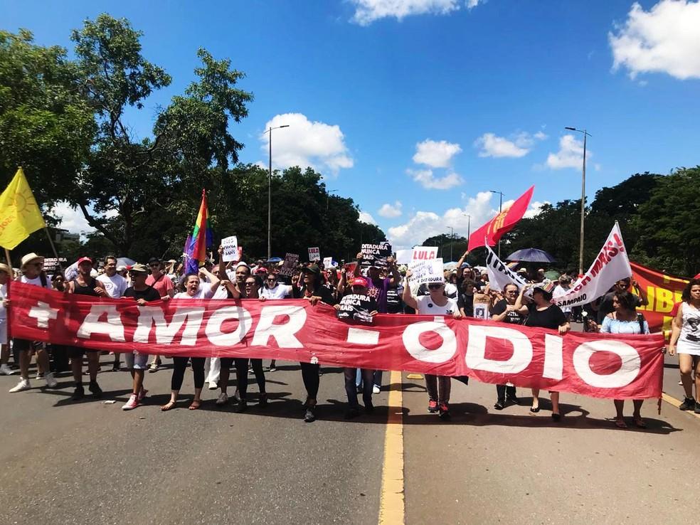Pessoas levam faixa escrita mais amor, menos ódio em ato contra a ditadura no Eixão Norte — Foto: Maria Nazaré Queiroz/Divulgação