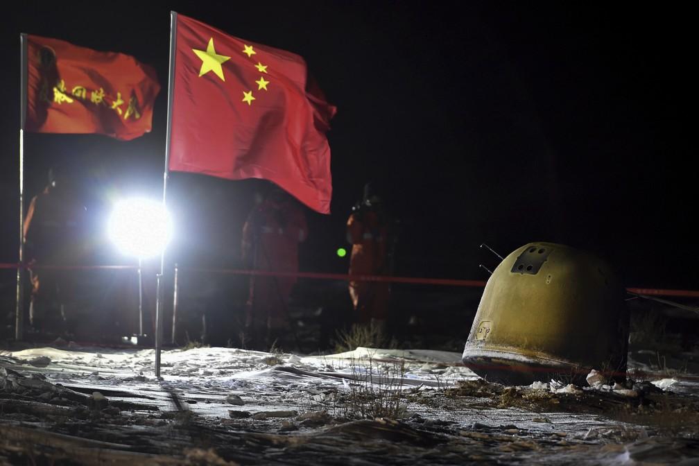 Na foto, divulgada nesta quinta-feira (17) pela agência de notícias chinesa Xinhua, membros da missão Chang'e 5 filmam a aterrissagem da sonda na província da Mongólia Interior, no norte da China.  — Foto: Ren Junchuan/Xinhua via AP