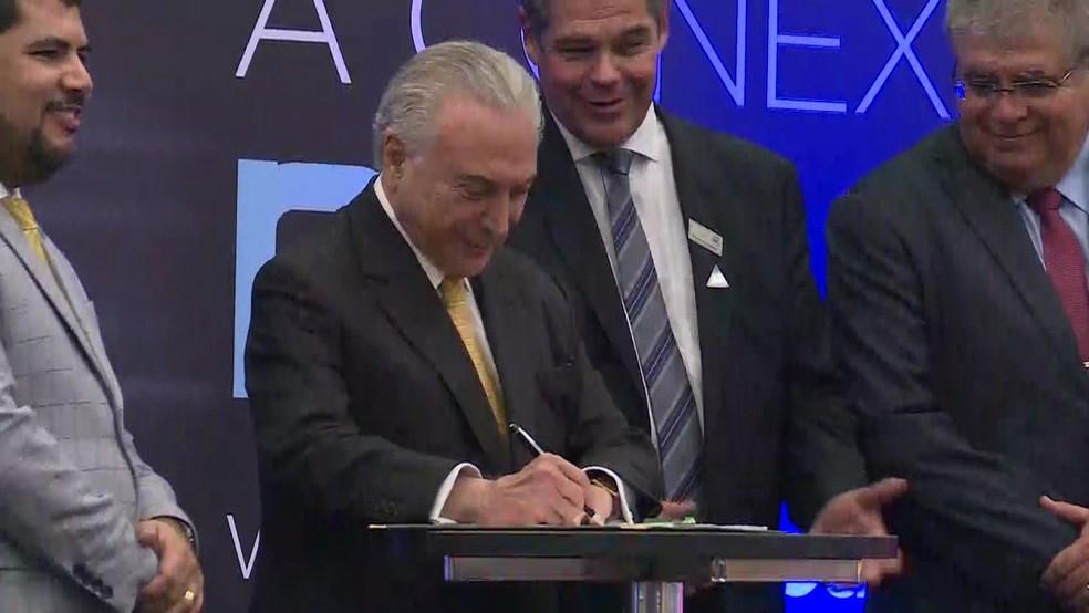 O presidente Michel Temer assina medida provisória no Salão Internacional do Automóvel em São Paulo — Foto: Reprodução/TV Globo