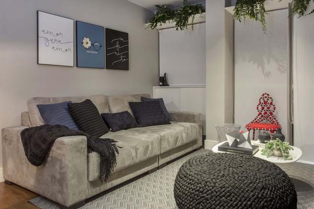 SALA DE ESTAR | O sofá cinza é da Harminy House, e as almofadas são da Codex (algumas são de acervo pessoal). A mesa de centro é da Oppa, e os enfeites em cima são da Dot Objetos e da Marché art de Vie. Os quadros e o vaso de cristal também são dessas duas lojas. O pufe é da Codex. A cadeira coral é assinada por Sergio Matos e é vendida na Marché Art de Vie.  (Foto: Mariana Orsi / Divulgação)