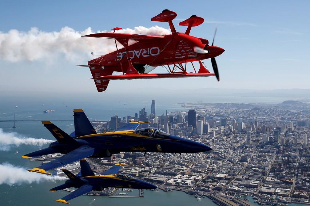 O esquadrão de demonstração de voo da Blue Navy Blue Angels e o piloto de acrobacias Sean Tucker, da equipe Oracle, voam sobre a Baía de São Francisco na Califórnia, EUA. Foto de quinta (5) divulgada nesta sexta (6) (Foto: Stephen Lam/Reuters)